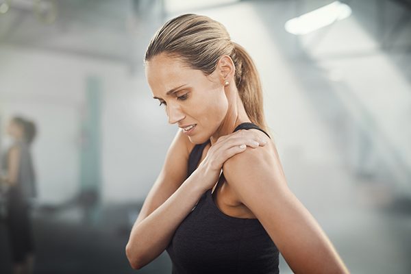 woman holding her shoulder in pain  what to eat after a workout