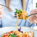 woman eating pasta | why are carbs important