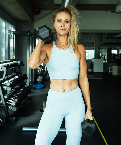kelsey posing with dumbbells