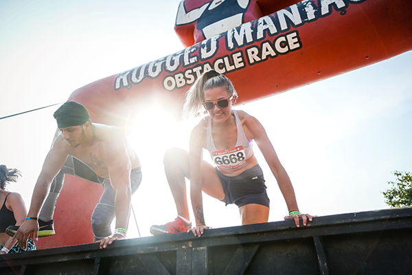 racers climbing over rugged maniac obstacle | openfit rugged maniac