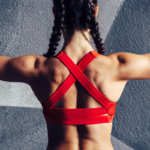 back view of female athlete flexing | bodyweight shoulder exercises