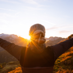 woman stretching arms looking at sunset   daily motivation