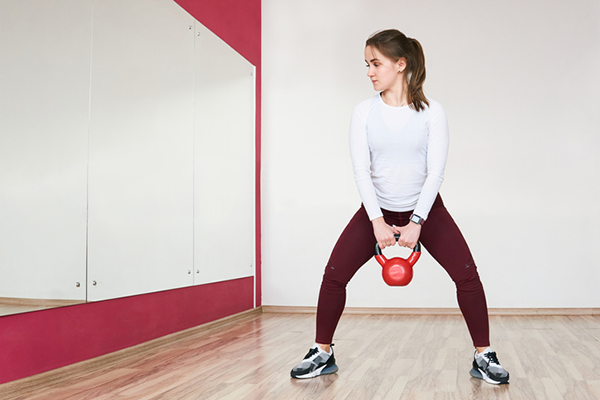 woman doing kettlebell squat looking in mirror | glute activation