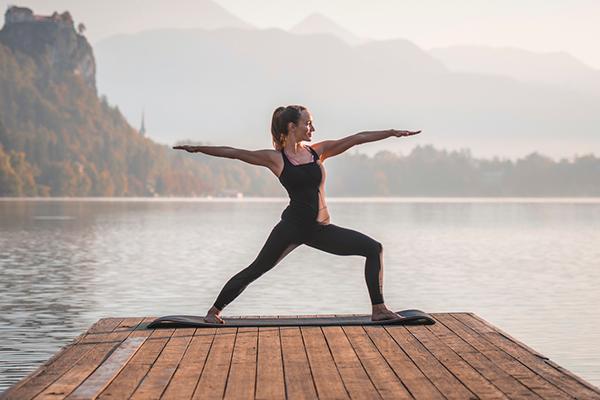 woman doing yoga on lake dock   post run yoga
