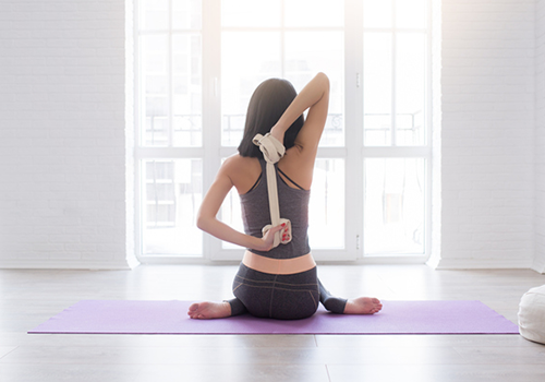woman stretching with yoga strap | how to increase flexibility