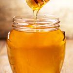 jar of honey next to honeycomb   benefits of honey