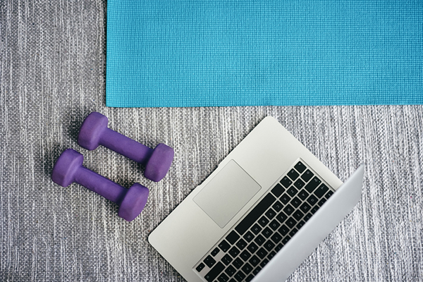 yoga mat and dumbbells in front of laptop | weight lifting workouts on openfit