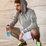 hooded man taking a break from exercise   how long to rest between sets