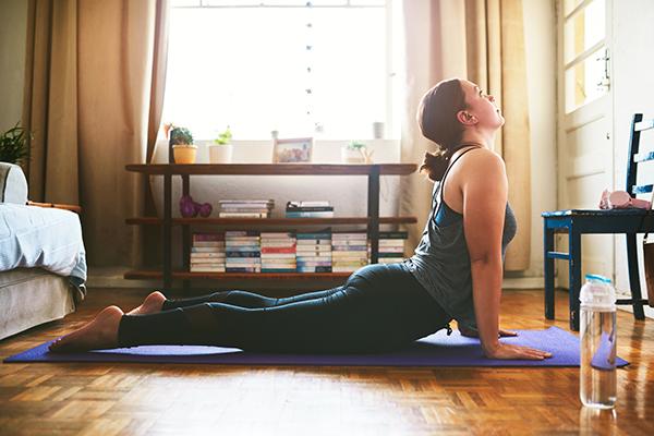 woman doing cobra pose on yoga mat   does stretching burn calories
