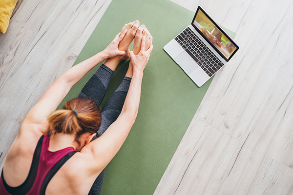 woman stretching in front of laptop   does stretching burn calories