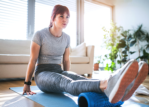 woman foam rolling at home