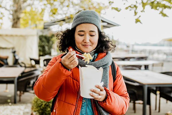 woman eating pasta to go | at what age does your metabolism slow down