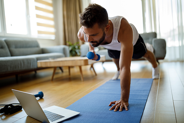 man lifting weights in front of laptop