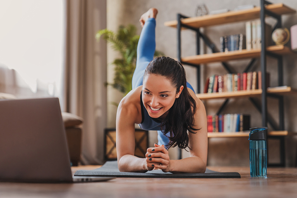 woman doing pilates in front of laptop