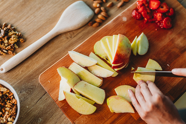 slicing apple on cutting board | low calorie snacks