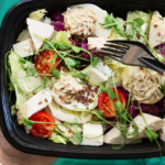 unpictured person holding plastic bowl of salad | trader joes salads