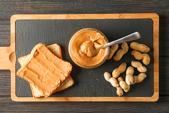 peanuts and peanut butter toast on cutting board | food allergies