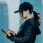 woman looking at phone with city skyline background