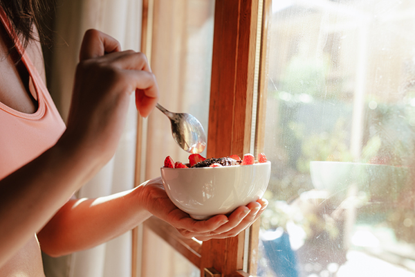 woman eating fruit yogurt bowl | cycling diet