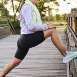 Woman stretching her hips before going on a run outside.
