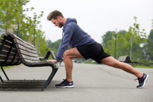 Man stretches against a park bench after going on a run | hip pain running