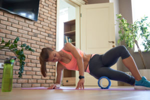 Athletic woman using a foam roller to stretch her hip | hip pain running