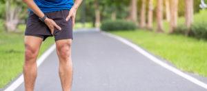 man grabs leg after running--avoid exercise injury