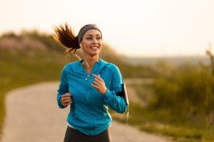 woman listening to music while running--running motivation