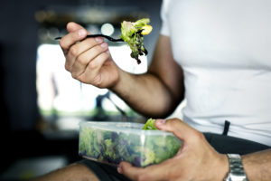 athlete eating salad after workout for fat loss -- body recomposition