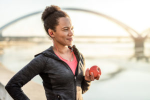 woman eating an apple on her jog -- what to eat before running