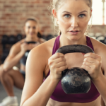 woman using kettle bell for weight training -- bodyweight vs weight training