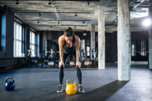 woman experiencing burn out with weights -- how to prevent exercise burnout