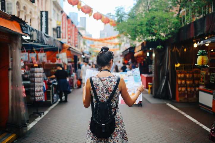 woman reading map while walking | how to treat yourself
