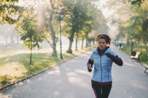 woman running in park -- how to avoid burnout