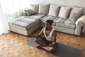man meditating in living room -- how often should you meditate