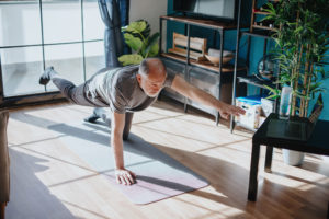 older man doing yoga -- can you prevent height loss with yoga -- does yoga make you taller