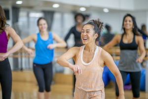 woman smiling in Zumba class -- exercise is stimulating -- what effect does exercise have on the nervous system