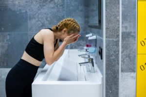 woman washing face at gym -- other benefits -- hot cold shower