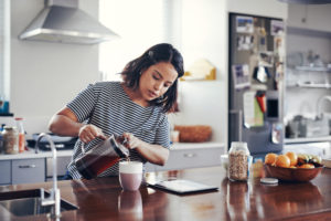 woman pouring coffee into cup -- too-much-caffeine